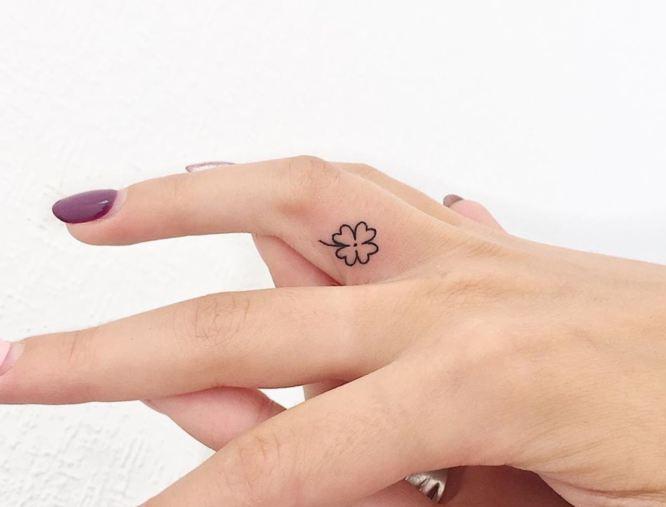 tatuaje trebol en los dedos